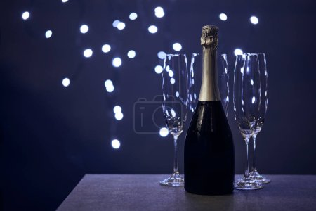 Photo for Bottle of champagne and glasses with blurred christmas lights - Royalty Free Image