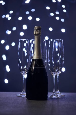Photo for Bottle of sparkling wine and glasses with blue christmas lights bokeh - Royalty Free Image