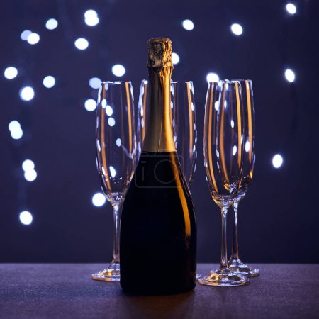 Photo for Bottle of champagne and glasses with christmas lights bokeh - Royalty Free Image