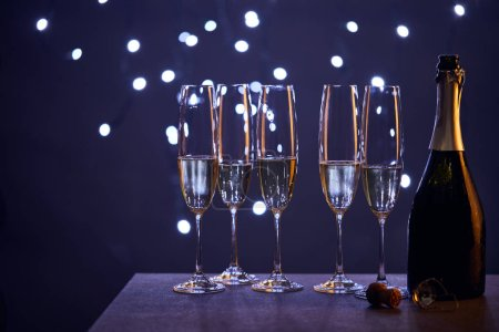 Photo for Sparkling wine in bottle and glasses with blue christmas lights bokeh - Royalty Free Image