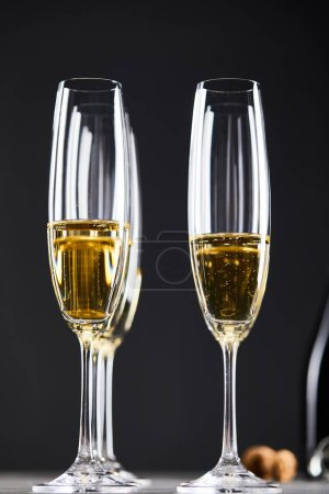 Photo for Close up of champagne in glasses for celebrating christmas eve on black - Royalty Free Image