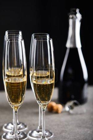Foto de Glasses and bottle of sparkling wine for celebrating christmas on black - Imagen libre de derechos