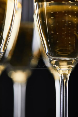 Photo pour Close up of glasses with champagne for celebrating christmas, isolated on black - image libre de droit