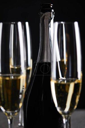 Photo pour Glasses and bottle of sparkling wine on black - image libre de droit