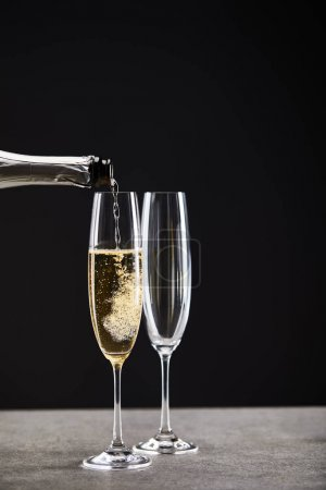 Photo for Close up of champagne pouring from bottle into glasses for celebrating christmas on black - Royalty Free Image