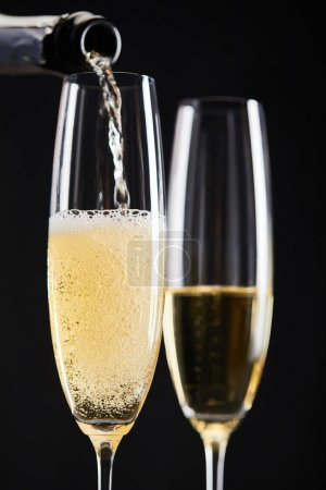 Photo pour Close up of champagne pouring into glasses for celebrating christmas, isolated on black - image libre de droit