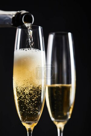 Photo pour Sparkling wine pouring from bottle into glasses for celebrating christmas, isolated on black - image libre de droit