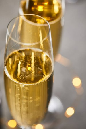 Photo for Close up of glasses of champagne with blurred yellow christmas lights - Royalty Free Image