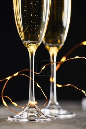 close up of traditional sparkling wine in glasses with yellow christmas lights, on black
