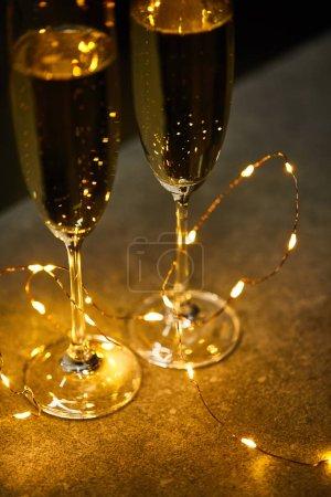 Foto de Vino espumoso tradicional en gafas con luces amarillas. - Imagen libre de derechos