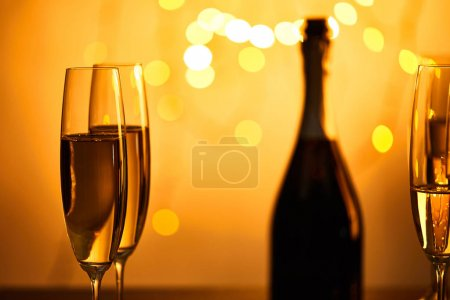 Photo for Glasses and bottle of champagne with yellow christmas lights bokeh - Royalty Free Image