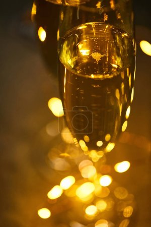 Photo pour Close up of glasses of sparkling wine with blurred yellow christmas lights - image libre de droit