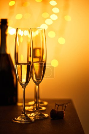 Photo for Cork, bottle and glasses with sparkling wine, with yellow christmas lights bokeh - Royalty Free Image