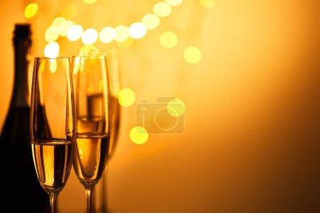 Foto de Vajilla y botella de vino espumoso con lámparas amarillas de capucha. - Imagen libre de derechos