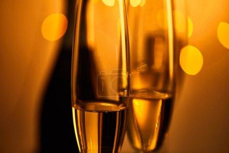 Photo pour Verres de vin mousseux avec bouteille floue et lumières de Noël jaunes - image libre de droit