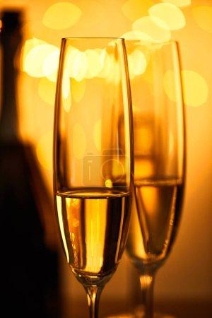 Foto de Gafas de champán con botella difuminada y luces de christmas amarillas. - Imagen libre de derechos