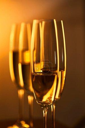 Photo pour Près des verres de champagne avec des lumières de Noël jaunes floues - image libre de droit