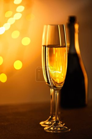 Photo for Glasses of champagne with blurred bottle and yellow christmas lights - Royalty Free Image