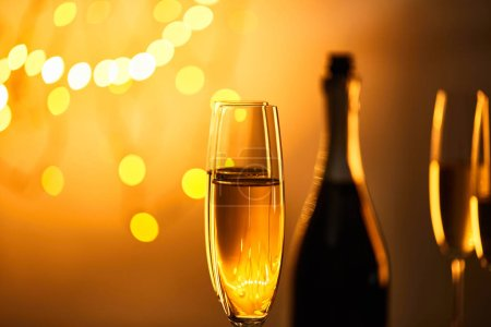 Photo for Glasses of sparkling wine with blurred bottle and yellow christmas lights - Royalty Free Image