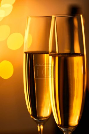 Photo for Glasses of sparkling wine with yellow christmas lights bokeh - Royalty Free Image
