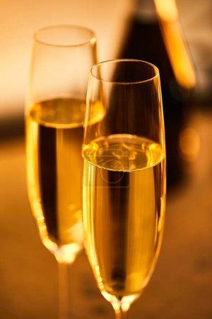 Photo pour Verres de champagne avec bouteille floue et lumières de Noël jaunes - image libre de droit