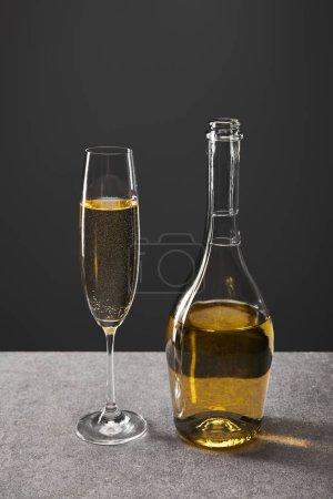 Foto de Vaso y botella de vino espumoso para celebrar las navidades en la víspera gris. - Imagen libre de derechos