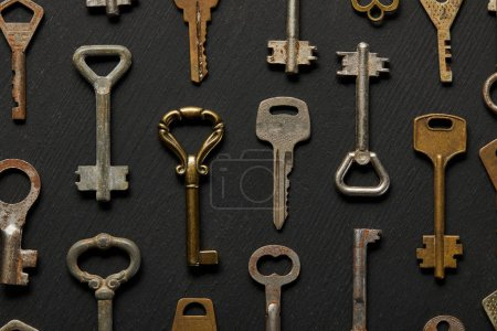 Photo for Top view of vintage rusty keys on black background - Royalty Free Image
