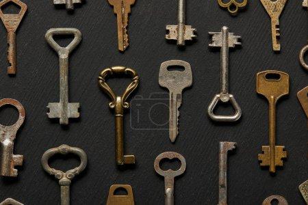 Photo pour Vue de dessus des clés rouillées vintage sur fond noir - image libre de droit