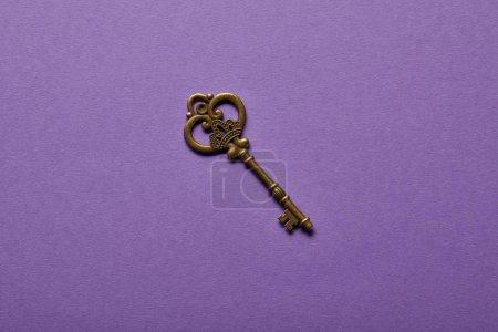 Photo pour Vue du dessus de la clé vintage sur fond violet - image libre de droit