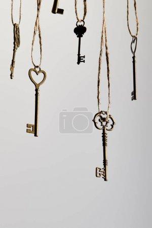 Photo pour Des clés d'époque suspendues sur des cordes isolées sur du blanc - image libre de droit