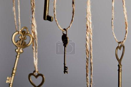 Photo pour Vue rapprochée des clés vintage suspendues aux cordes isolées sur gris - image libre de droit