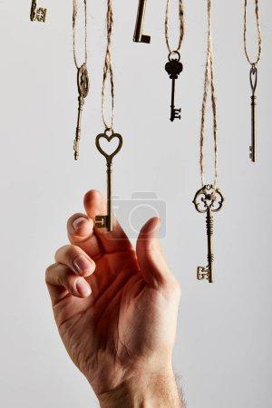 Photo pour Crochet vue d'un homme touchant des clés d'époque accrochées à des cordes isolées sur du blanc - image libre de droit