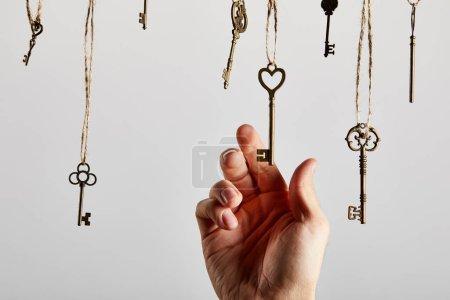 Photo pour Vue recadrée de l'homme touchant clés vintage suspendues sur des cordes isolées sur blanc - image libre de droit
