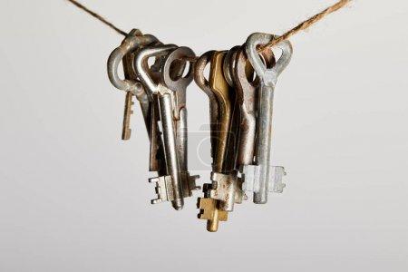 Photo pour Clés rouillées vintage accrochées à une corde isolée sur blanc - image libre de droit