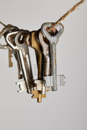 Photo for Close up view of vintage rusty keys hanging on rope isolated on white - Royalty Free Image