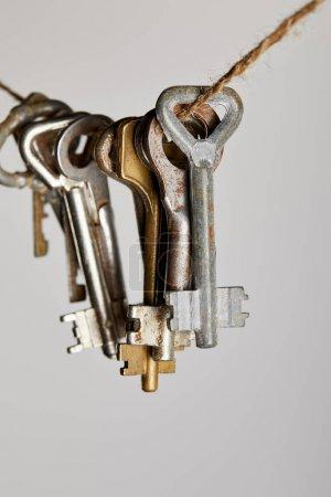 Photo pour Vue rapprochée des clés rouillées vintage suspendues à une corde isolée sur blanc - image libre de droit