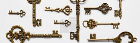 Photo pour Top view of vintage keys on white background, panoramic shot - image libre de droit