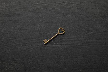 Photo pour Vue de dessus de la clé rouillée vintage avec coeur sur fond noir - image libre de droit