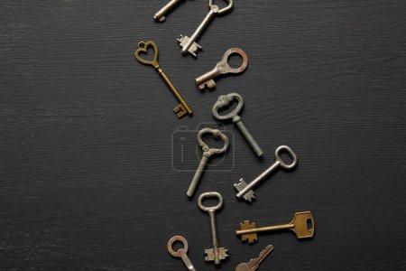 Foto de Vista superior de las llaves oxidadas de la época en el fondo negro - Imagen libre de derechos