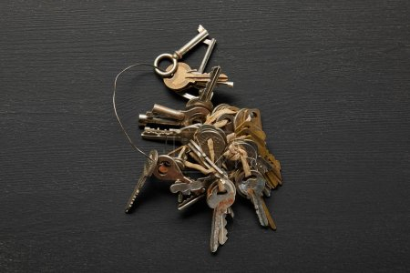 Photo for Top view of vintage rusty keys in bunch on black background - Royalty Free Image