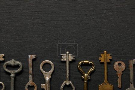 Photo pour Pose plate avec des clés rouillées vintage sur fond noir - image libre de droit