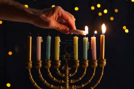 Photo pour Cropped view of man lighting up candles in menorah on black background with bokeh lights on Hanukkah - image libre de droit