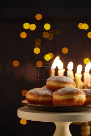 Photo for Selective focus of delicious doughnuts on stand near glowing candles on black background with bokeh lights on Hanukkah - Royalty Free Image