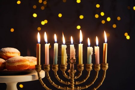 Photo pour Delicious doughnuts on stand near glowing candles in menorah on black background with bokeh lights on Hanukkah - image libre de droit