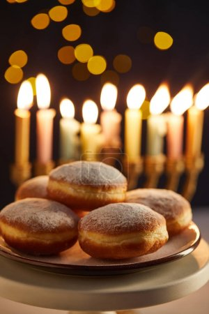 selective focus of delicious doughnuts on stand near glowing candles on black background with bokeh lights on Hanukkah