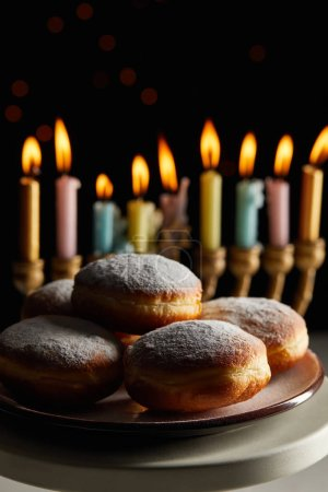 Photo for Selective focus of delicious doughnuts on stand near glowing candles in menorah on black background with bokeh lights on Hanukkah - Royalty Free Image