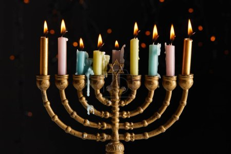 Photo pour Glowing candles in menorah on black background with bokeh lights on Hanukkah - image libre de droit