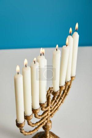 Photo pour Brûlant des bougies dans menorah isolé sur bleu - image libre de droit