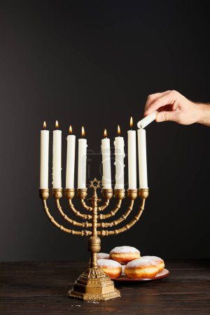 Photo for Cropped view of man lighting up candles in menorah near doughnuts on black background on Hanukkah - Royalty Free Image