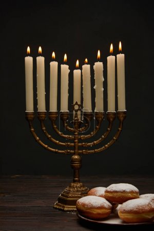 Photo pour Delicious doughnuts near burning candles in menorah on Hanukkah isolated on black - image libre de droit